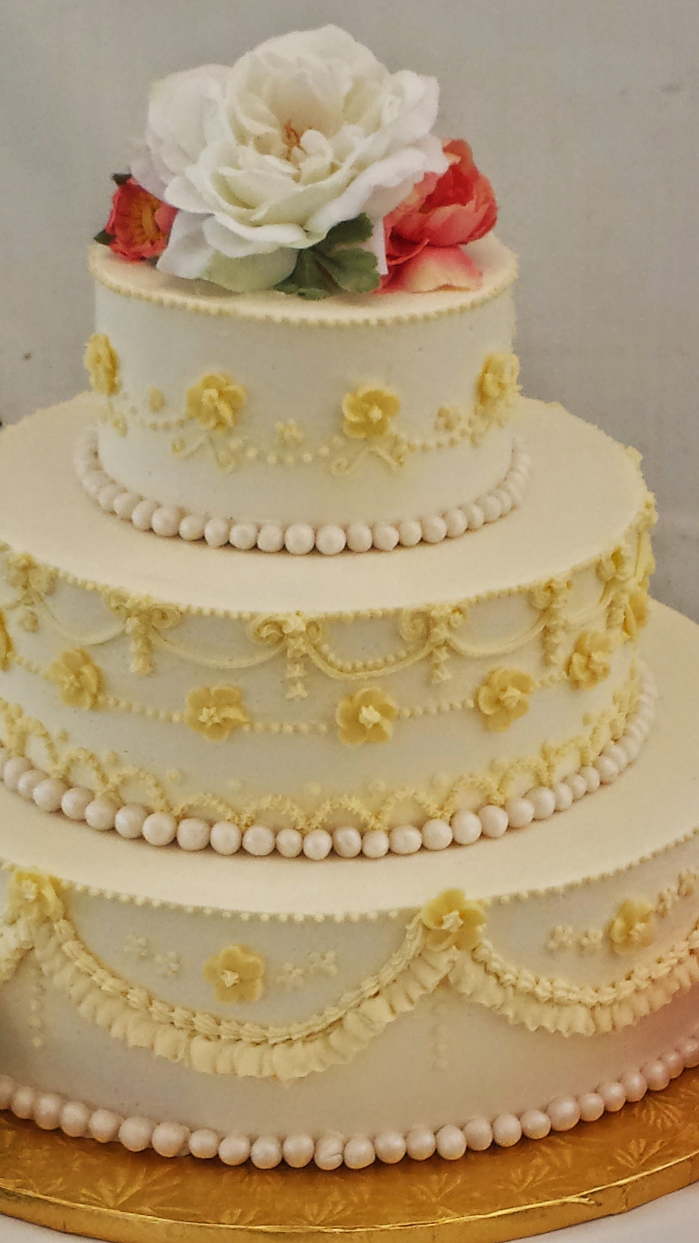 This princess-styled gold and white chocolate wedding cake is ...