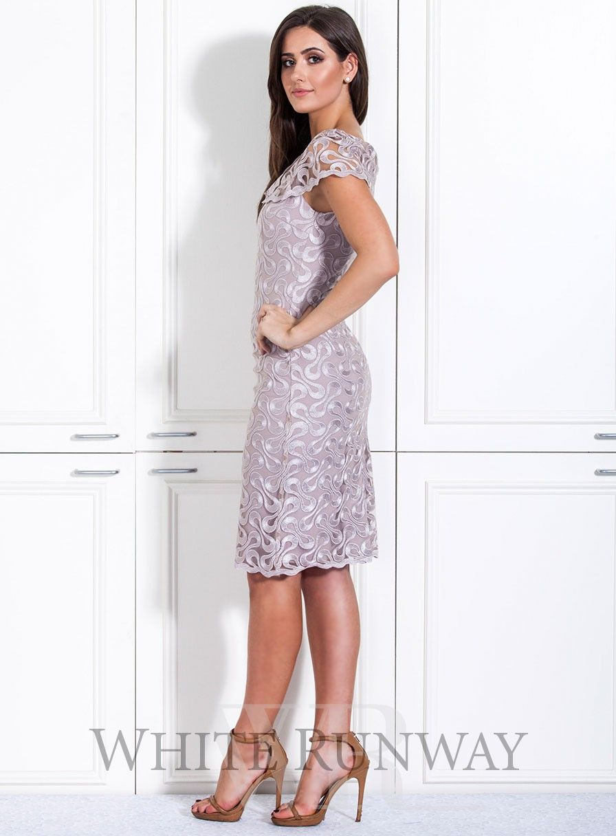 A stunning cocktail dress by Laura K. A high neck style made of an embroidered lace. #whiterunway #motherofthebride #weddingguestguest