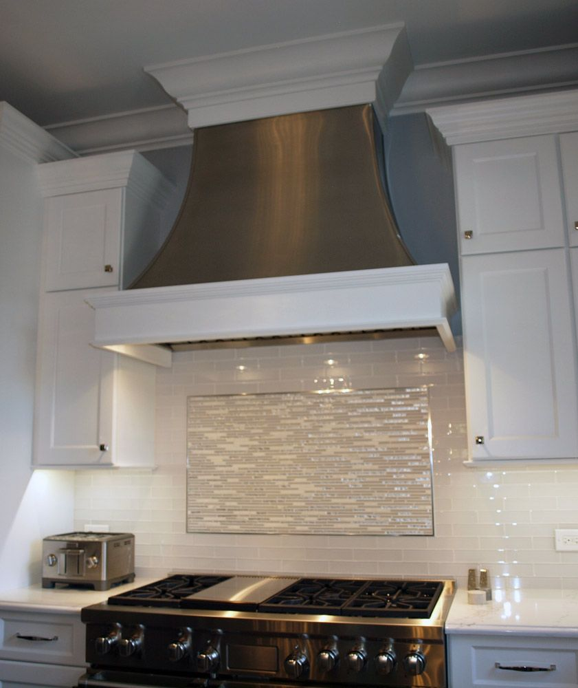 A Custom Metal Range Hood With Decorative Wood Trim Shows