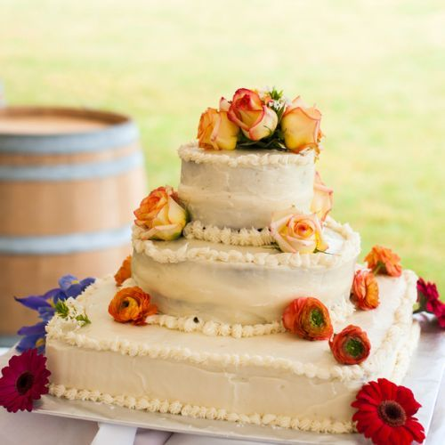 Real Weddings - In Bliss Weddings  Lucy Bartlett made a beautiful ivory buttercream cake with light orange roses, orange ranunculus, and red daisies to create a subtle ombre effect.   Image Credit: Cariad Photography