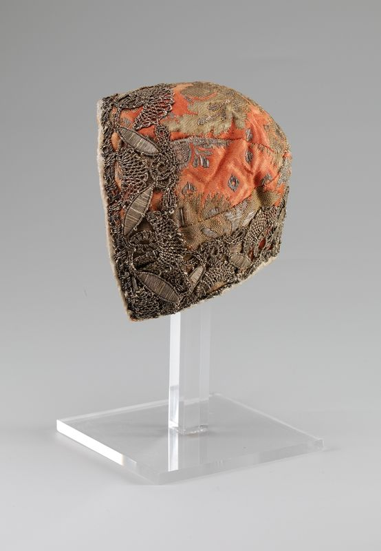 Infant's cap, Norway, 1730-1750. Orange silk brocade, decorated with metallic lace.