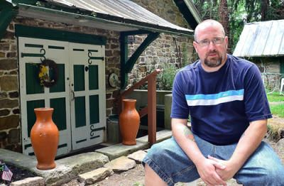 """Blake Stough sits in front of the historic Shady Lane distillery in East Manchester Township. Stough, the creator of the blog """"Preserving York,"""" is trying to piece together the history industrialist Frederick Small's property."""