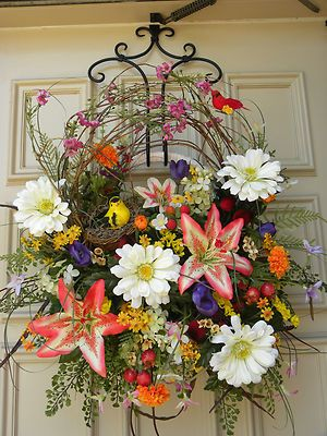 This is a half basket i filled with greenery, lilies, white zinnias, orange pomps, yellowish orange filler flower, a hint of purple and I brought honeysuckle vine up over the handle and added a red cardinal and a nest with a goldfinch in it.