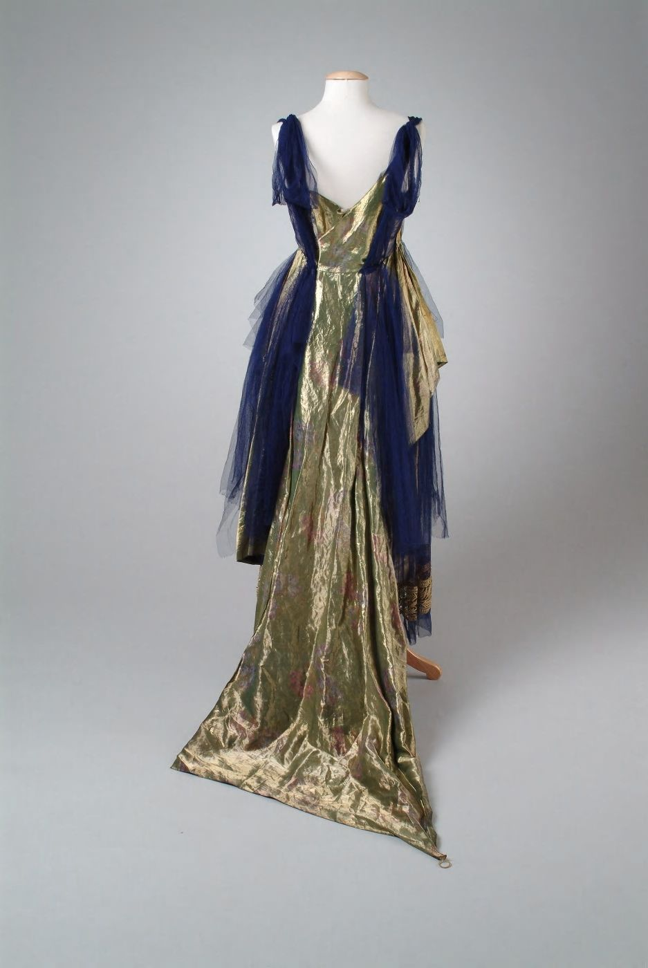 Dress:1921 Description: Evening gown of green gold metallic tissues woven with pink flowers. The under-skirt and trim are of violet silk illusion, creating an eighteenth century effect of panniers. The under-skirt is trimmed with gold bullion braid. A shorter over-skirt dips to a full train in the back. Back