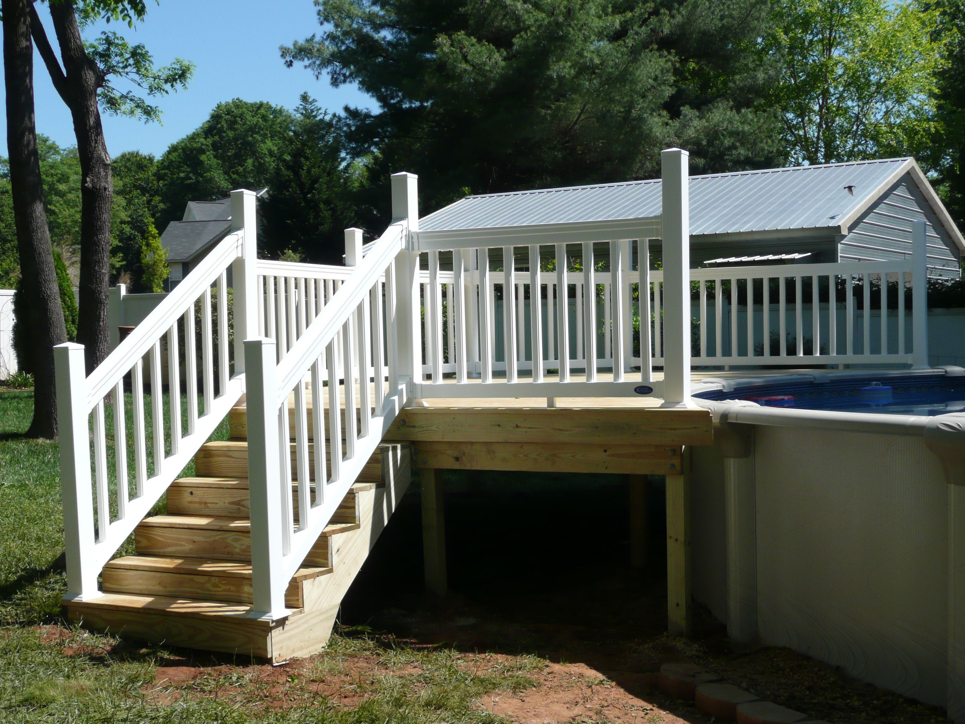Treated Wood Deck On Girders With White Vinyl Railing