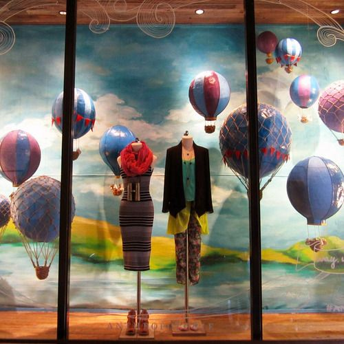What a thrill it would be to soar across the sky, nothing but a basket beneath your feet, way above the marshmallow clouds, marveling at the beauty of the world below. This spring, our store window…