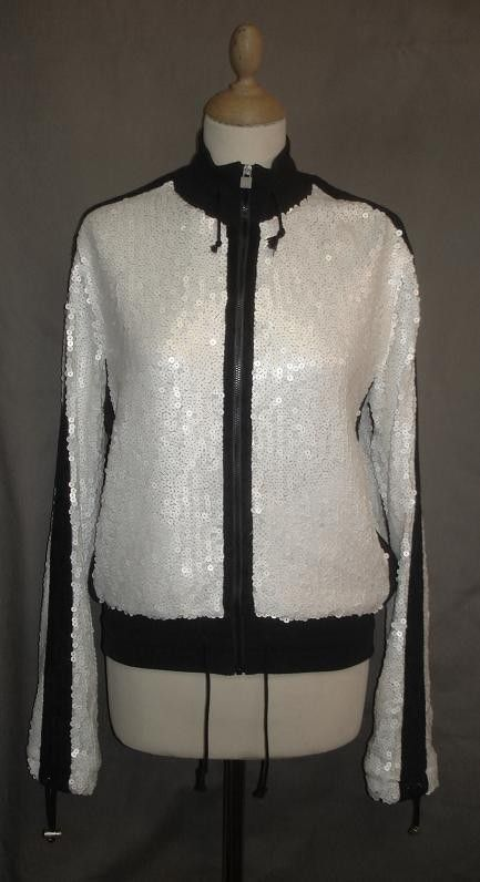 2,299.00 This Chanel white sequins sports jacket was part of the 2008 Cruise runway collection. Closes with a zipper closure on the front and features navy ribbed collar and hem.