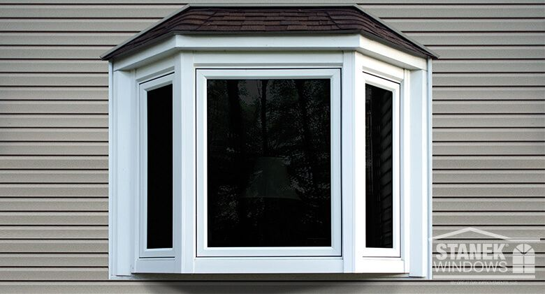 White bay window with shingled hip roof, casement end