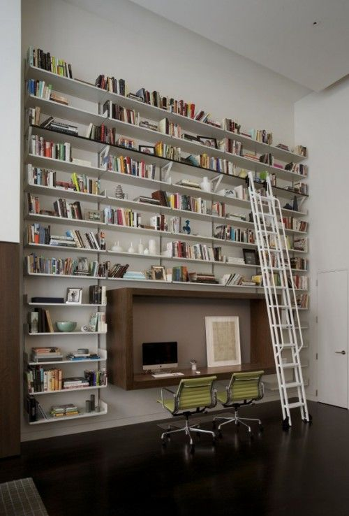 Very tall wall of shelves with ladder in modern home office
