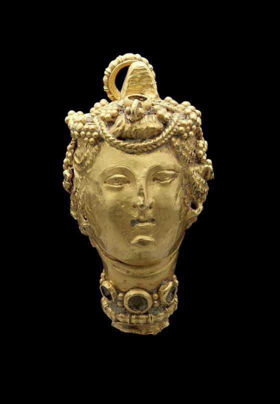 A Greek gold pendant terminal Circa 4th Century B.C. | Depicting a female head, with chased and repoussé details, her wavy hair enlivened with granulation and incision, wearing a cabochon necklace, the gems now missing, with hemispherical granulated suspension loop.