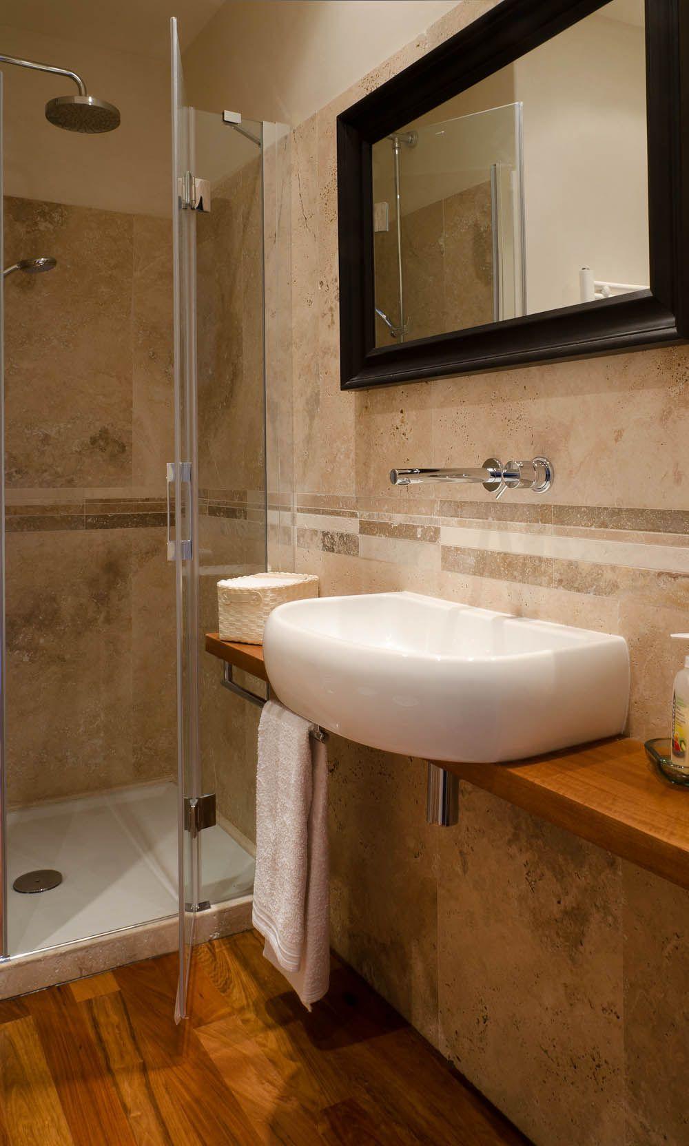 Bagno con rivestimento in travertino e pavimento in legno - Bagno rivestimento pietra ...