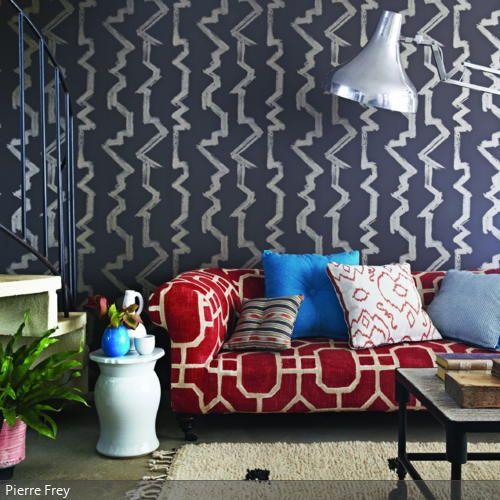 Die verschiedenen Muster der grauen Tapete, des roten Sofas und der ...