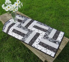 This Table runner is made from a collection of 4 different Black and White fabrics The backing is made with made from a white fabric with bold,