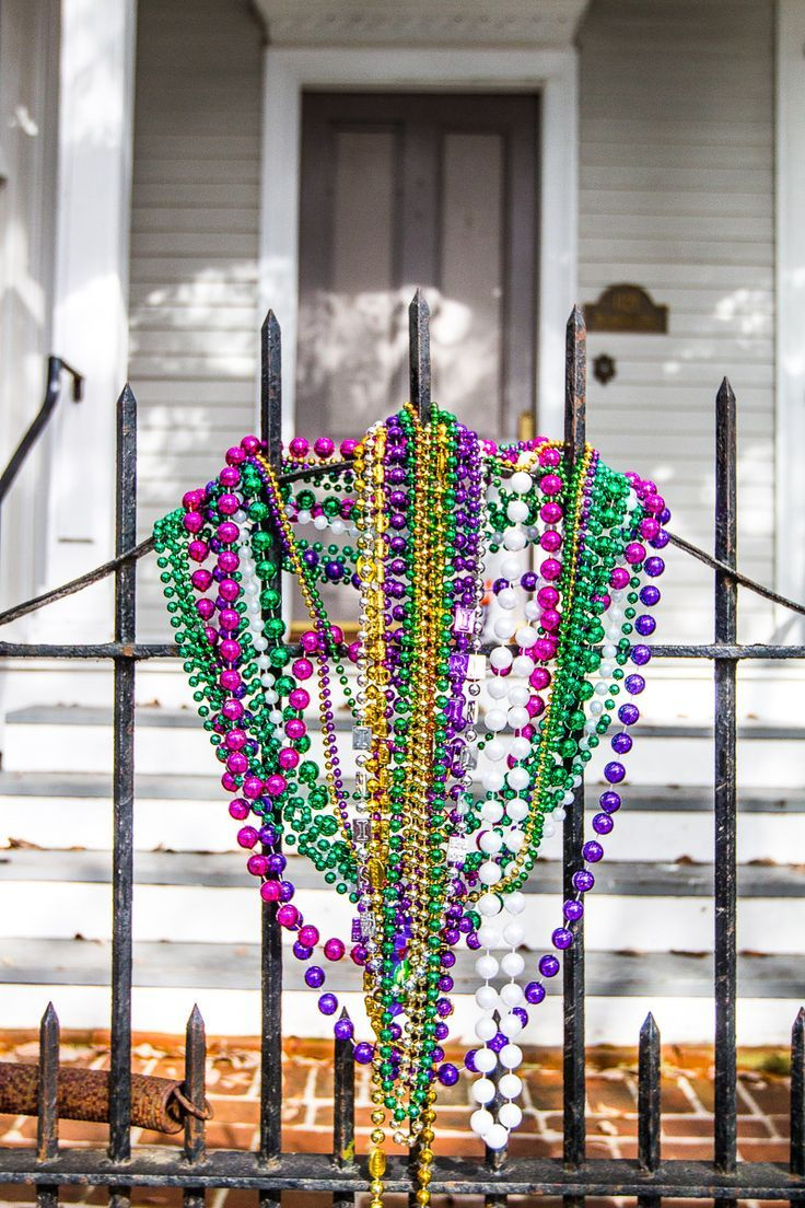 Mardi Gras beads in The Historic Garden District of New Orleans. Such a beautiful neighborhood to walk around in The Big Easy with kids. #familytravel #neworleans #travel #mardigras