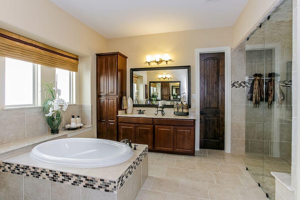 gehan homes master bathroom dark wood cabinets drop in tub tan tile