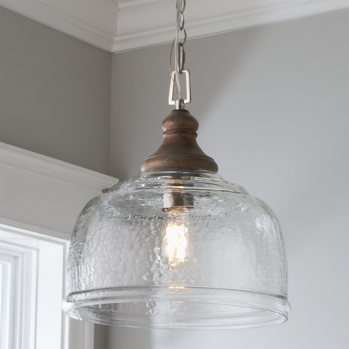 Eclectic and contemporary, this pendant can accommodate any space.  The rippled glass shade elevates the overall fixture.  The organic, gray washed wood cap provides a natural element to this unique pendant .