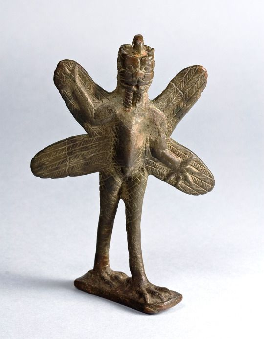 """Neo-Assyrian Bronze Pazuzu Figurine, c. 800-600 BC The demon Pazuzu represented by this figurine stands like a human but has a scorpion's body, feathered wings and legs, talons, and a lion-like face on both front and back. In Assyrian and Babylonian mythology Pazuzu, the """"king of the evil wind demons,"""" was not entirely unfriendly to mankind."""