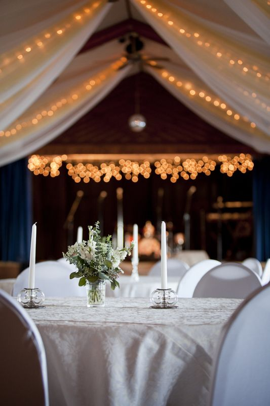 Elegant Indoor Wedding Reception Venue With Simple Table Decor Complemented By Drapes And String Lights