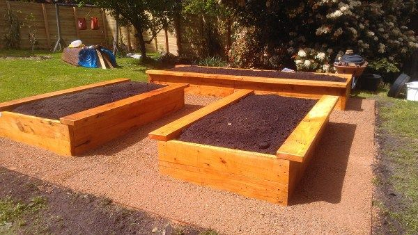 Raised cypress veggie beds bordered by crushed stone ...
