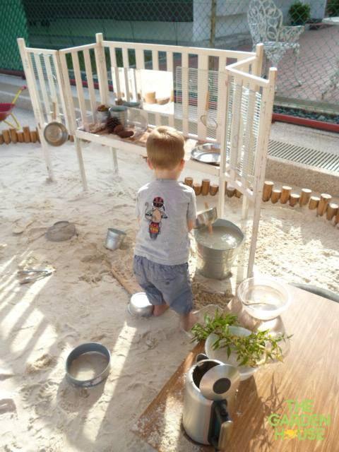 "I love the little log stumps surrounding this sand kitchen - at The Garden House Preschool ("",)"