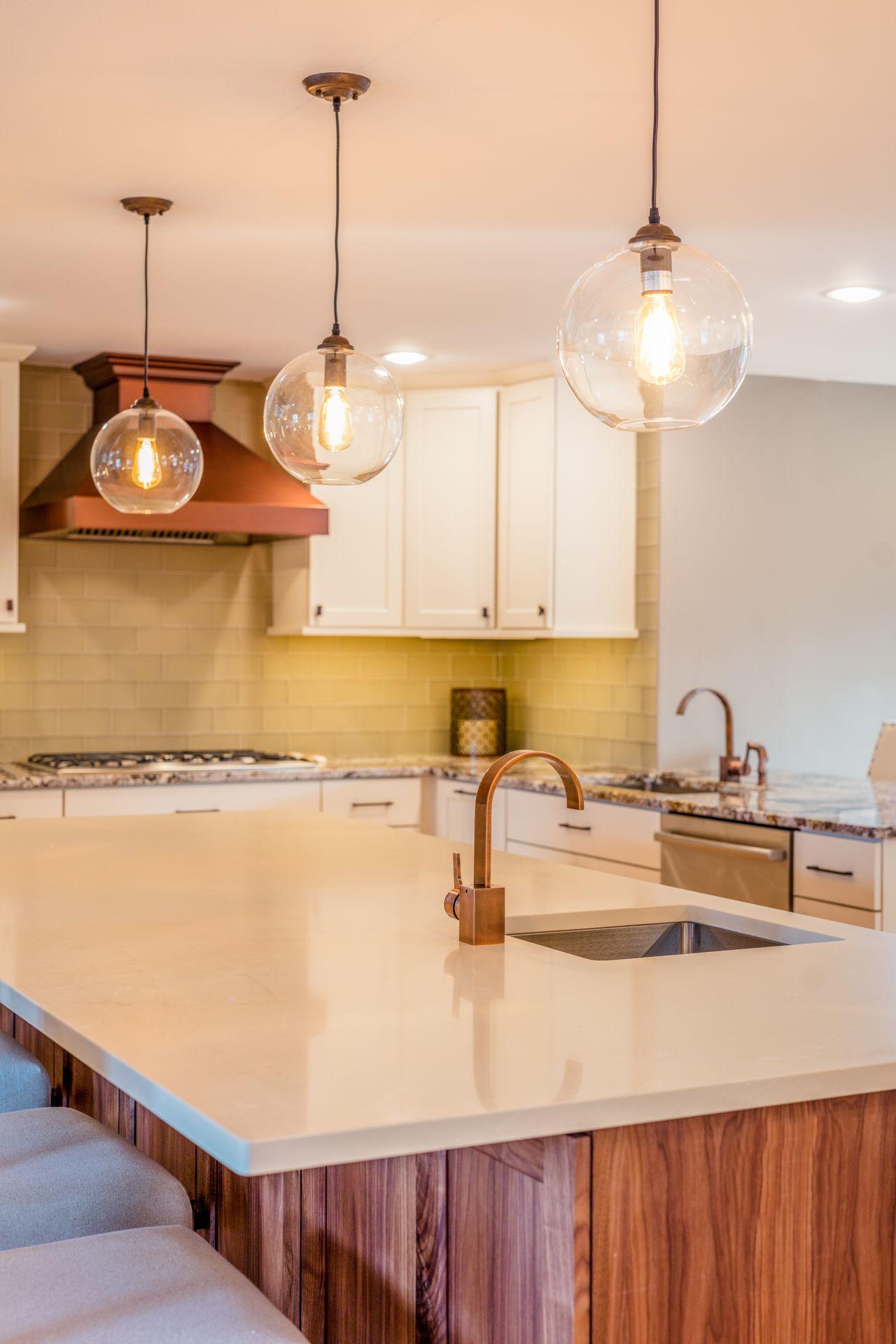 Clear Globe Lights Over Walnut Island Copper Kitchen