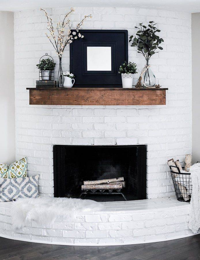 Get ideas for decorating a spring fireplace that will last as a summer mantel too. See how our fireplace's white bricks pop against this farmhouse style mantel setup. Easy DIY decorating with simple flower arrangements and rustic decor. Centered with a modern navy mirror, this fireplace mantel will inspire you! #springfireplacedecor #summermantel