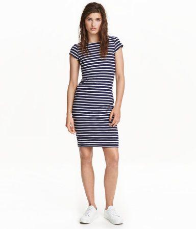 Mørk blå/Hvit stripet. En kort, figurnær kjole i myk bomullstrikot. Kjolen er dypt ringet bak og har korte ermer.