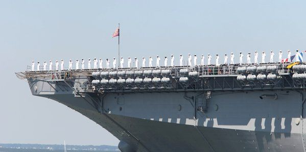 Sailors aboard USS Wasp greet crews of U.S. Coast Guard Tall Ship Eagle during OpSail 2012. (Sangjib Min / June 8, 2012)
