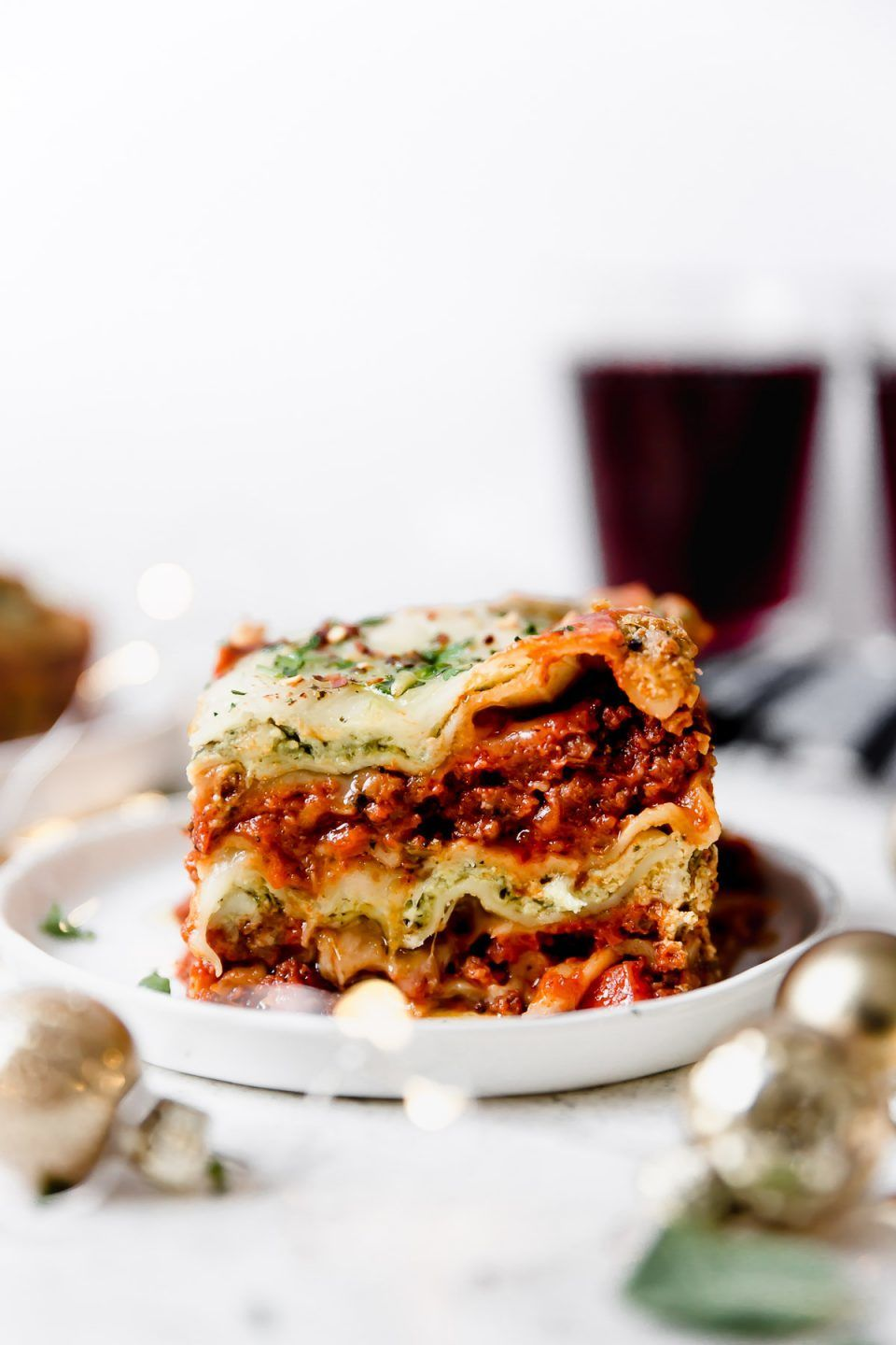 The most festive lasagna you'll ever meet: Christmas Eve Lasagna! A twist on classic lasagna bolognese, this lasagna boasts festive red & green layers of rich & hearty homemade bolognese sauce & basil pesto ricotta. Equally stunning & delicious, this Christmas Eve Lasagna is the perfect dish to make for any holiday dinner. #lasagnarecipe #classiclasagna #christmasdinner #christmasrecipes