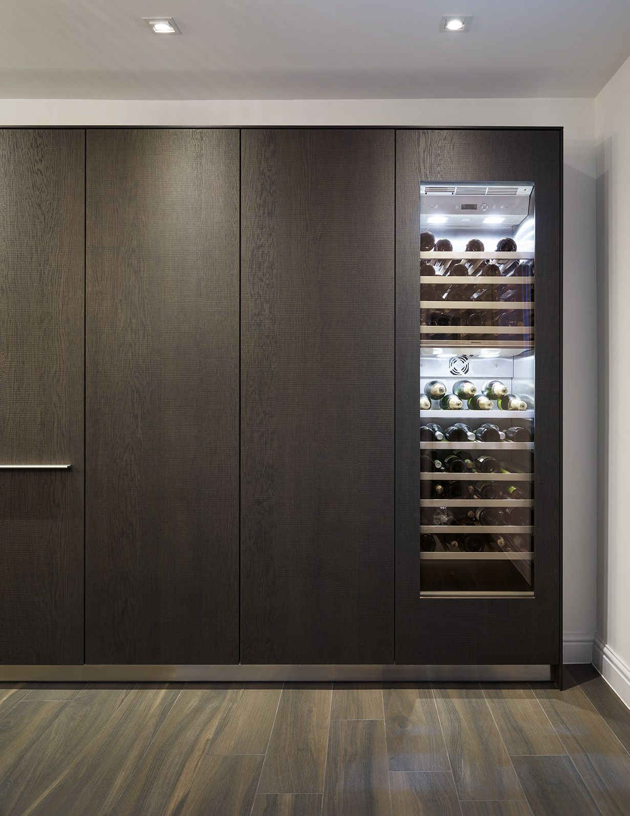 Tall, dark wood kitchen units provide great storage and also house a ...
