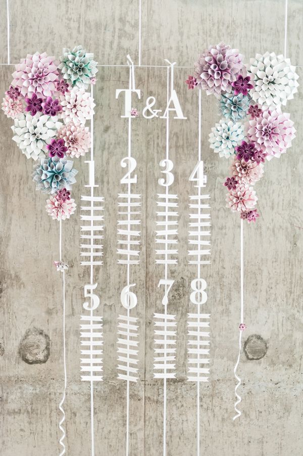 Pretty hanging escort card display. Love those paper flowers!