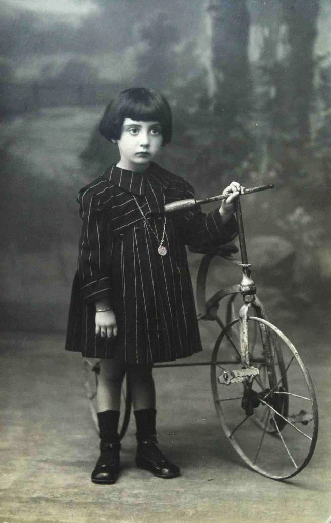 Vintage photo postcard, young girl with a tricycle