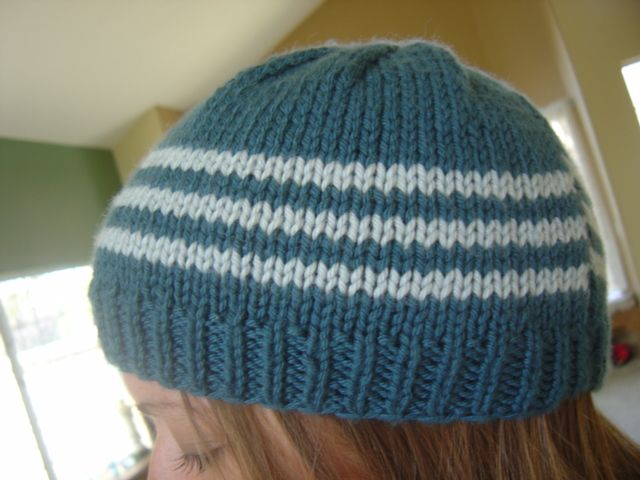 Materials:1 ball of Debbie Bliss Cashmerino Aran in MC (Teal) and a small amount in CC (Light Blue) for stripes.US Size 7 and US Size 9 straight needles.Pattern:With MC and size 7 needles, cast on …