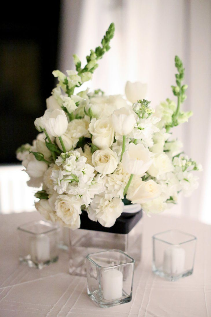 All white centerpieces of tulips roses carnations and