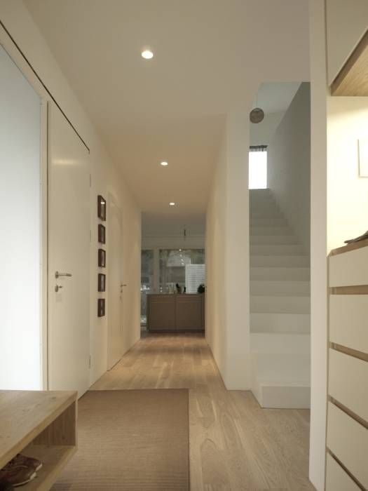 Eingestellter Treppenkörper als Zonierung: Minimalistisch Flur, Diele & Treppenhaus von Viktor Filimonow Architekt in München