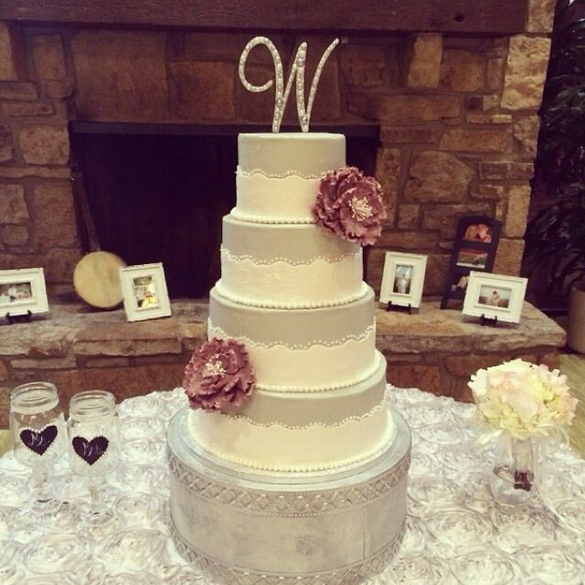 This 4 tier cake has a scalloped ribbon with a lace impression that ...