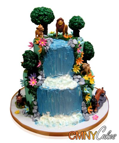 Two Tiered Cake With Lion King Toys This magnificent cake was made for a birthday party. We were so excited to try out our abilities on a theme of nature as it was something really different.  We started with a base in white fondant surrounded by a brown ribbon. We then placed two tiers onto the base. We created a waterfall effect in blue fondant flowing down from the top of the cake to the .... http://cmnycakes.com/gallery2/v/Cakes+For+All+Occasions/Two+Tiered+Cake+With+Lion+King+Toys.html?