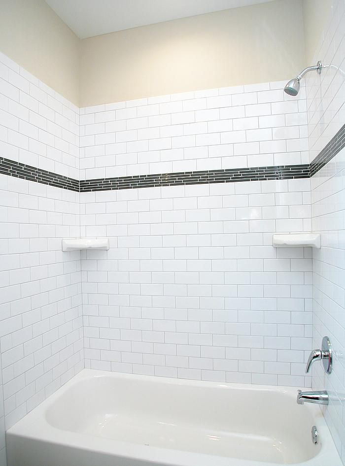 A Modern Style Tub With Subway Tile Surround With Glass Tile Accent Strip There Are Two Built In Patterned Bathroom Tiles Bathtub Tile Surround Bathtub Tile