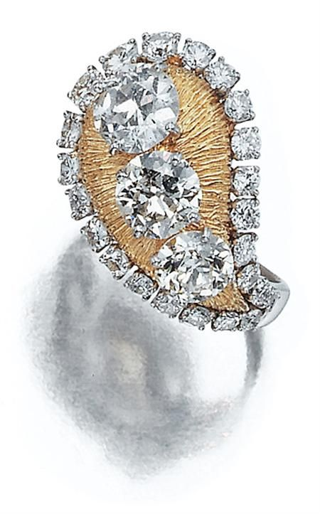 Lot 3392 Platinum, Gold and Diamond Ring, Ruser The textured gold teardrop-shaped panel centering 3 old European-cut diamonds approximately 3.70 cts., edged and flanked by 37 platinum-set round and single-cut diamonds approximately 2.10 cts., completed by a platinum shank, signed Ruser.
