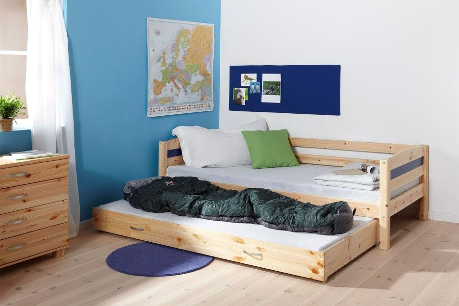 Furniture Unstained Pine Wood Pallet Trundle Bed Combined With Wooden Chest Of Drawer Plus Rounded Blue Door Mat On Untreated Harwood Floor