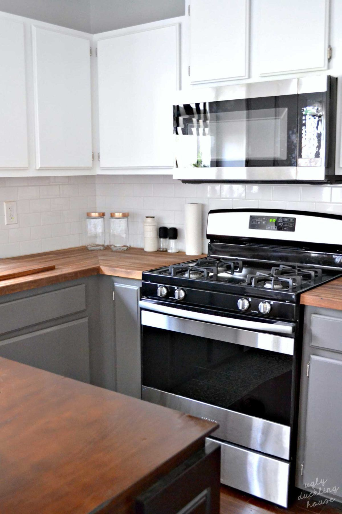 WOW! White and gray kitchen with stainless and black appliances... love the butcher block countertop the most. #kitchen #diykitchen #kitcheninspiration #whitecabinets #80skitchen #kitchenmakeover #beforeandafter #butcherblock #graycabinets