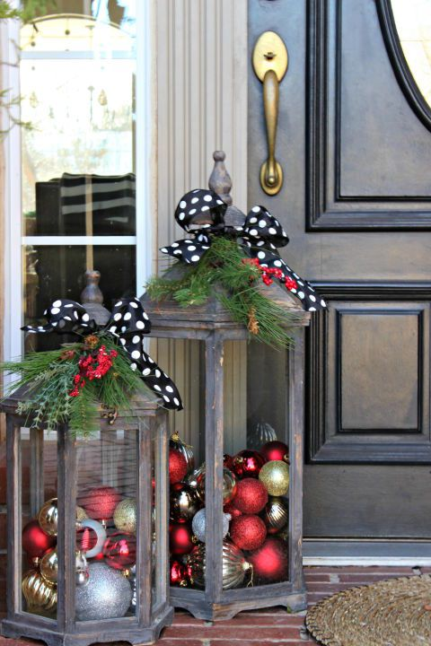 give your front door the city glam you love by filling lanterns with shiny ornaments and adorning them with a black and white polka dot ribbon