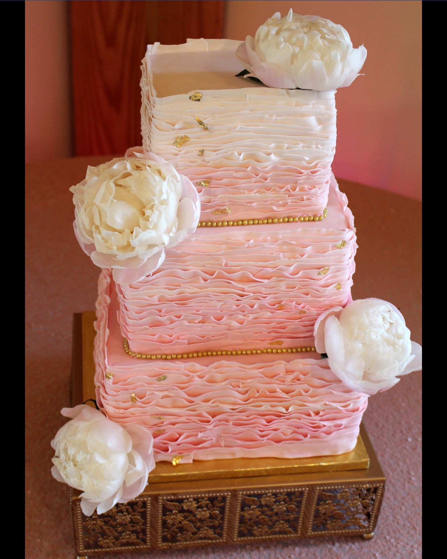 Pink ombre ruffle wedding cake with edible gold details and peonies ...