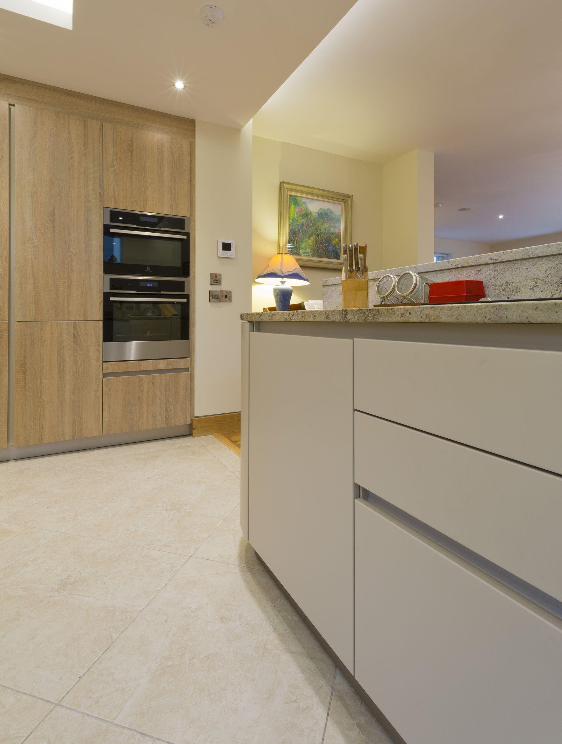 A Schuller Kitchen With Champagne Matt Base Units And Samo Oak Natural Brown Imitation Larder Units Topped With An Est Contemporary Kitchen Kitchen Larder Unit