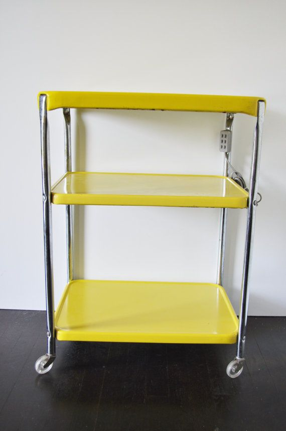 {yellow tri-level cart} vintage with electrical outlet! Had one of these in white when I was first married. Toaster on the top shelf, waffle iron on the second shelf and upright rotisserie on the bottom shelf.