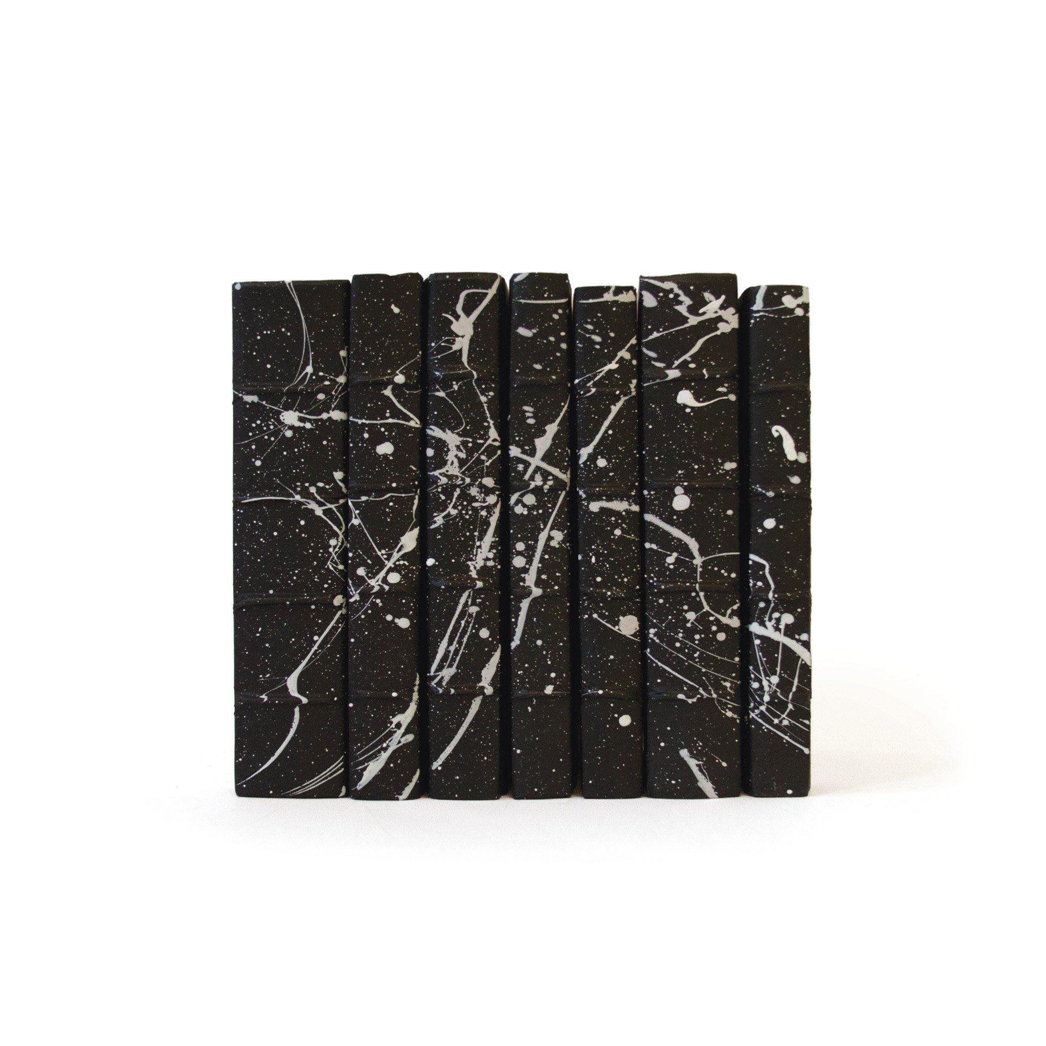 Dekorative Pergamentbücher – Ein linearer Fuß – Weißer Spritzer auf Schwarz