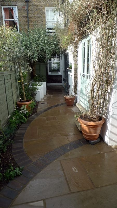 Indian sandstone paving cut into curves with brick edge for Paving ideas for small courtyards