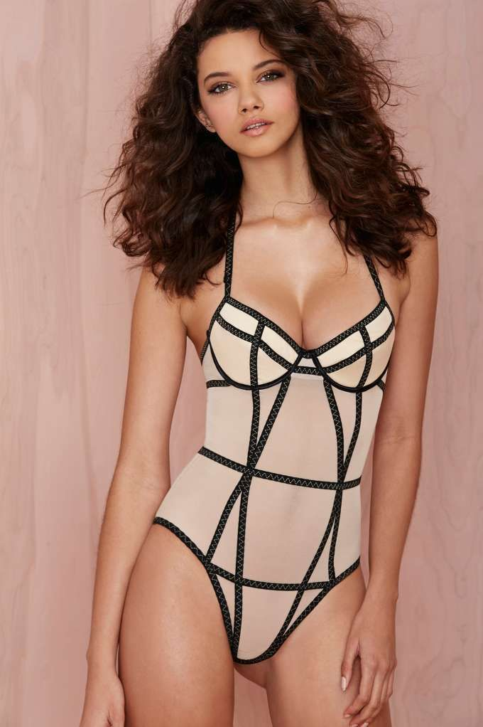 3f03b4bed149 Look like the ultimate Bond girl in this nude bodysuit featuring black cage  straps with contrast stitching.