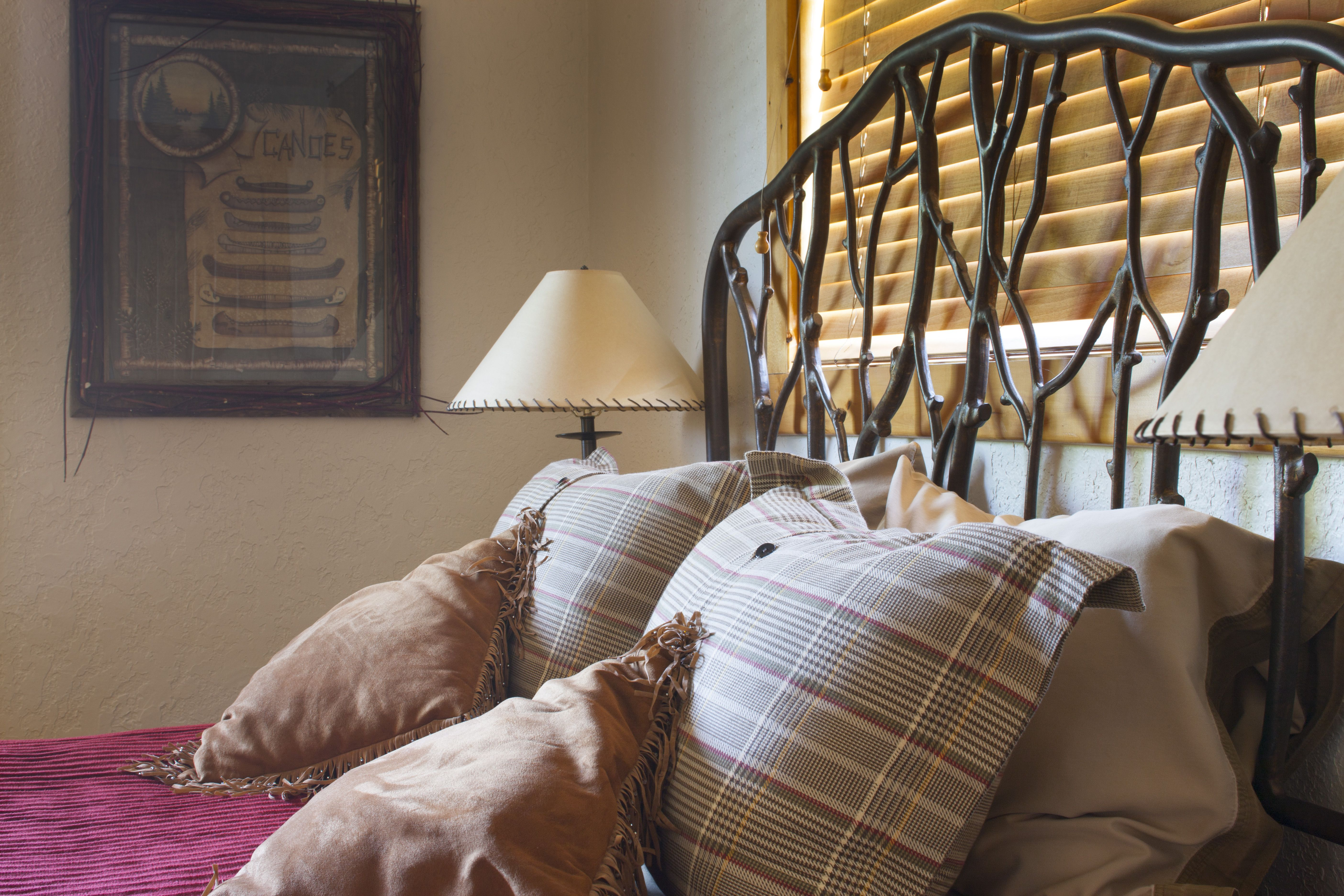 Metal twig headboard anchors the queen master bed. Bed