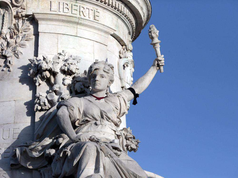 A black armband is tied around the arm of a relief adoring the plinth of the statue of Marianne at the Place de la Republique, on January 11, 2015 in Paris.